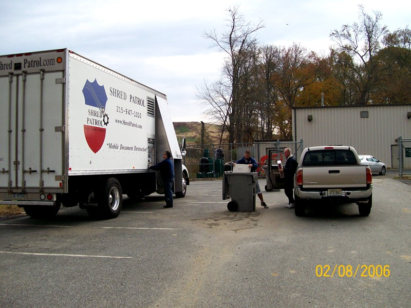Paper shredding truck with people dropping off documents