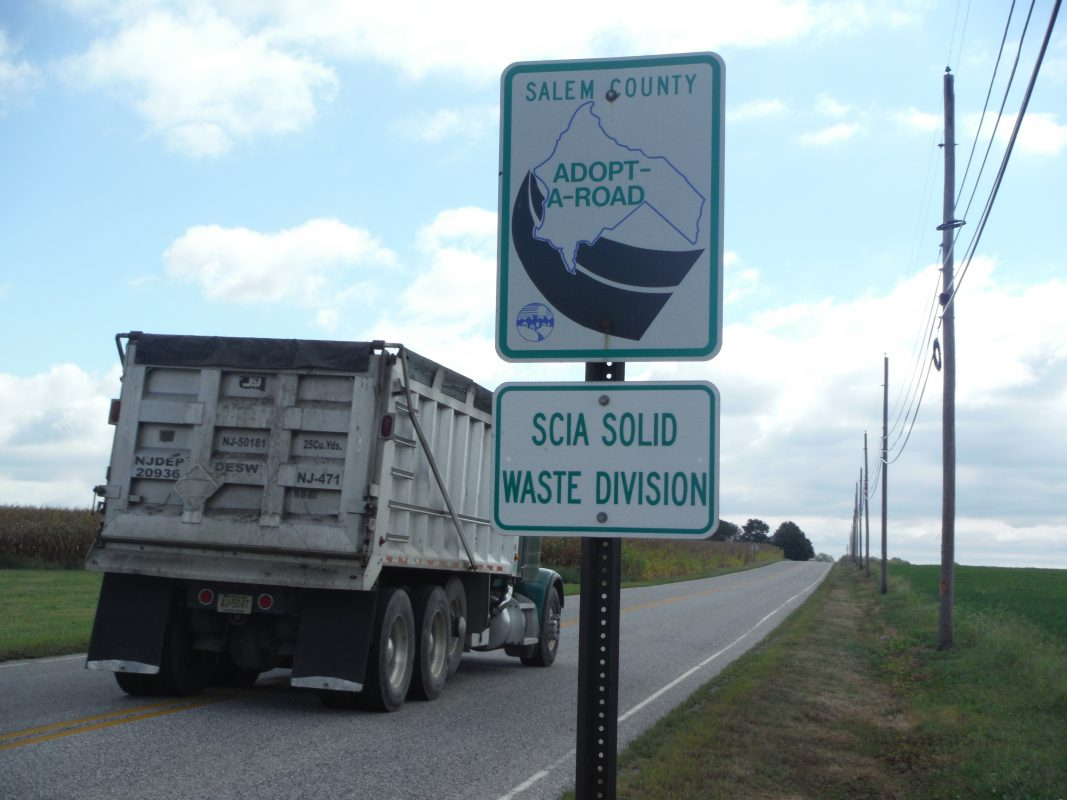 Adopt a road sign with a dump truck driving past