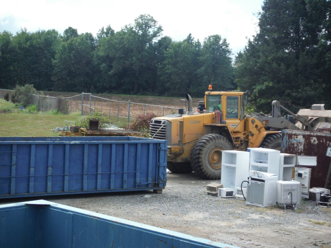 A bulldozer moving dumpters