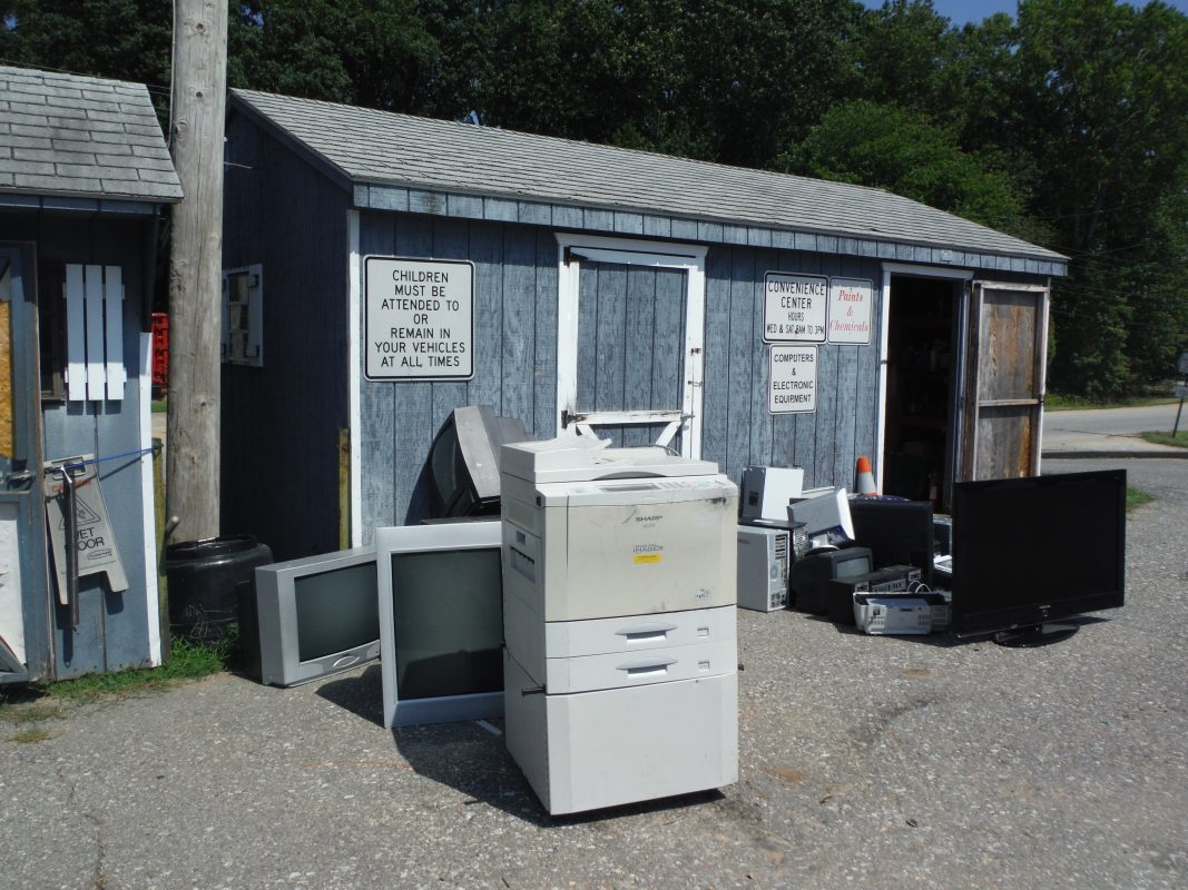 Electronic recycling shed with a large office copier and TVs sitting in front