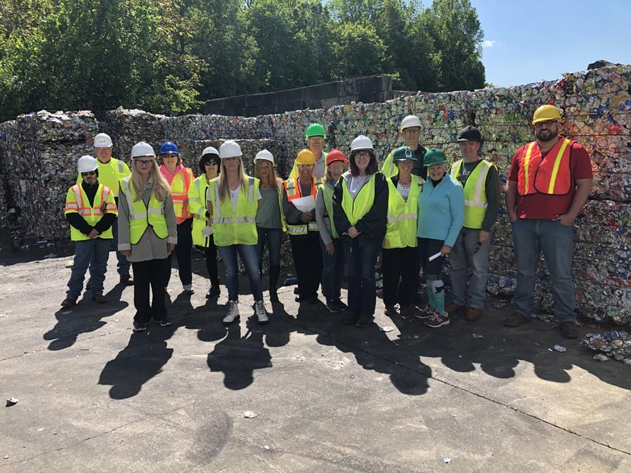 Workers with hardhats posing in front of bales of recyclables