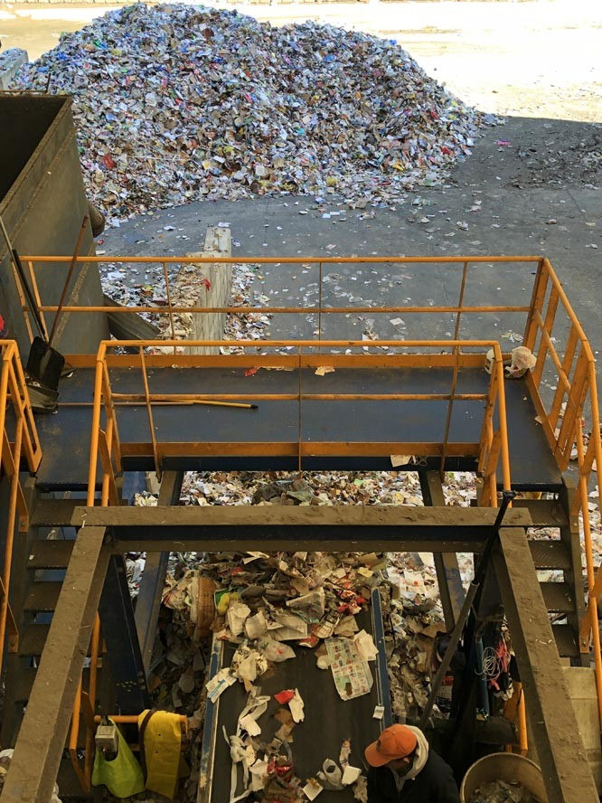 Pile of recycled material on floor and worker sorting material on conveyer belt