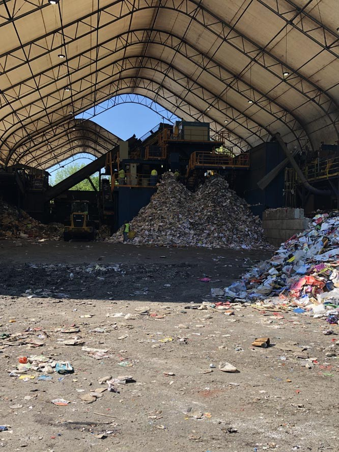 Machinery inside of covered building with pile of recycle paper in frontof it