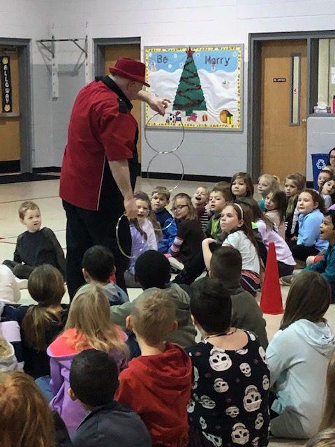 Magician doing metal loop trick for school kids sitting on the floor