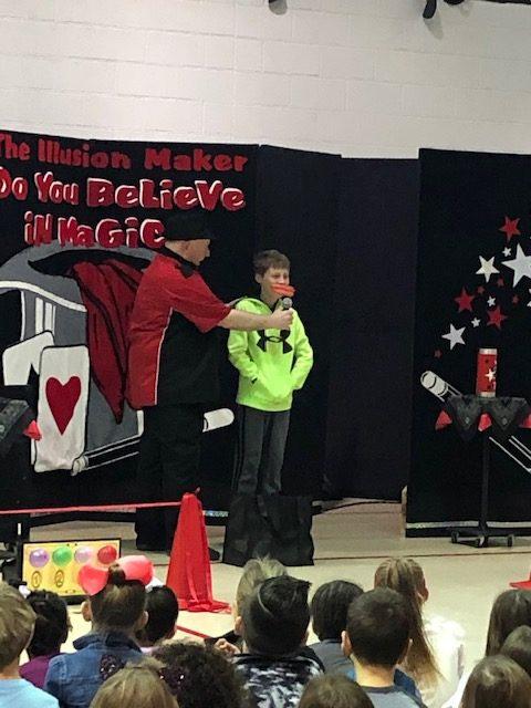 Magician has young man working with him in front of crowd of school kids
