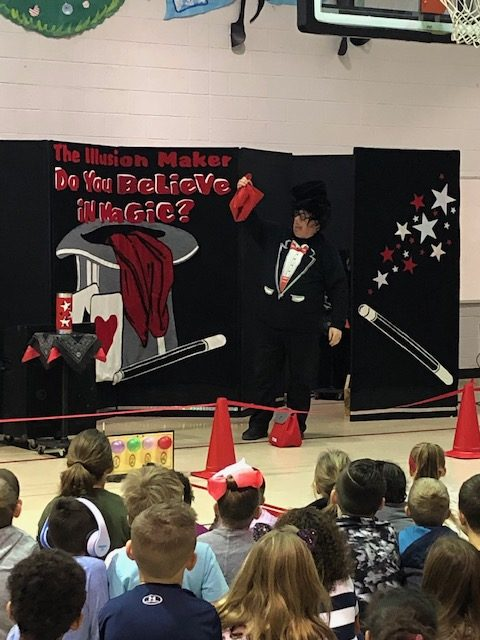 Magician in front of school children with a banner