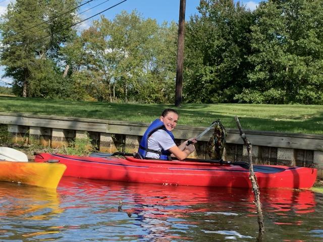 Child in red kayak in lake along grassline