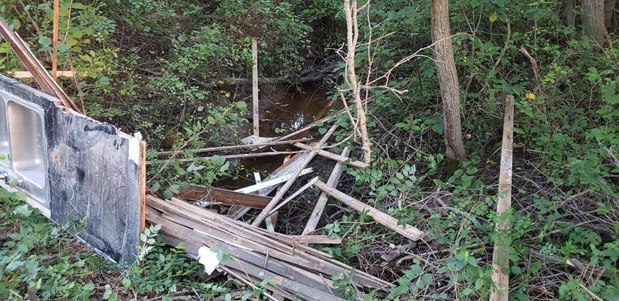 Pile of broken wooden planks in creek
