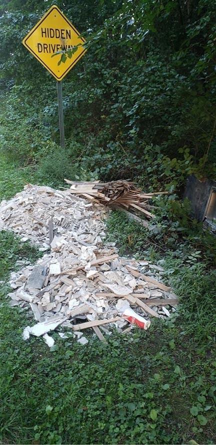 Pile of broken planks and drywall in creek