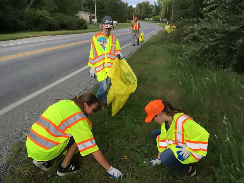 Girl Scout Troop cleaning up litter along road